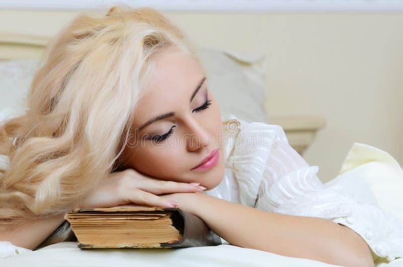 Het mooie meisje op een bed royalty-vrije stock foto's