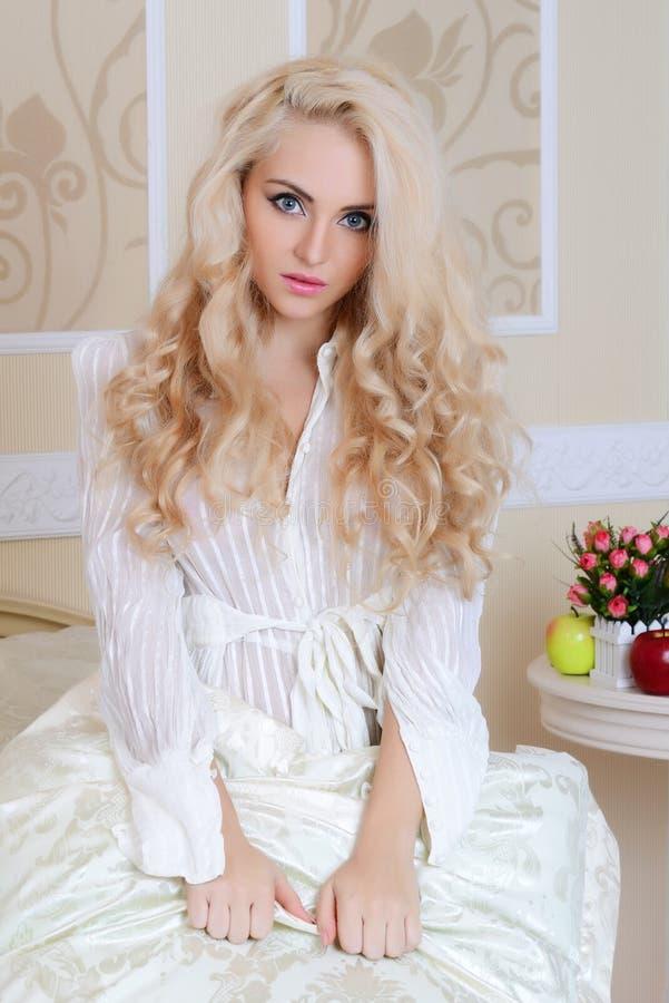 Het mooie meisje op een bed stock afbeelding