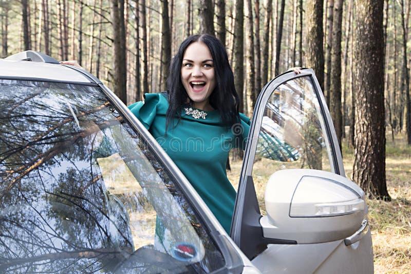 Het mooie meisje opent de autodeur stock afbeelding