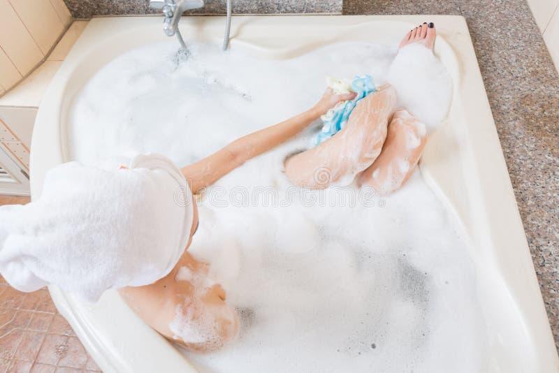 Het mooie meisje overgieten en het wassen dienen badkuip in stock foto