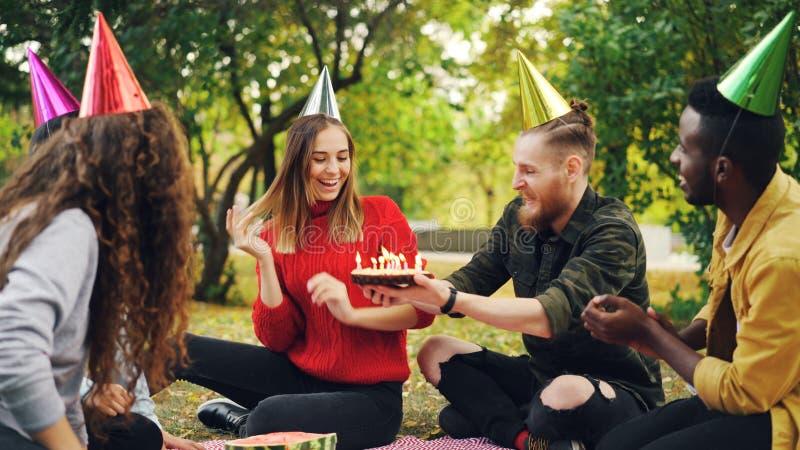 Het mooie meisje in partijhoed viert verjaardag met vrienden in park op picknick die wens maken, blazend kaarsen op cake stock fotografie