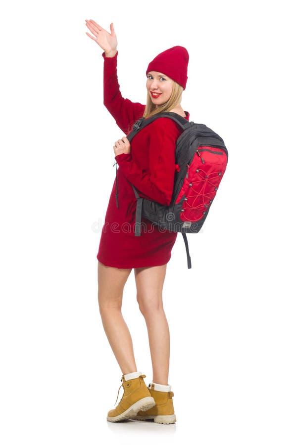 Het mooie meisje in rode die kleding en rugzak op wit wordt geïsoleerd stock afbeelding