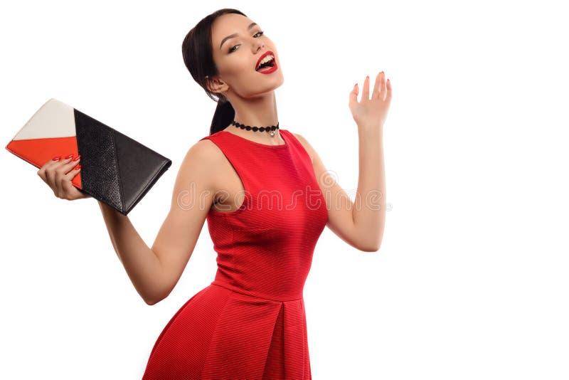 Het mooie meisje in rode kleding met kleurrijke koppeling geniet van verkoop die op witte achtergrond wordt geïsoleerd stock foto's