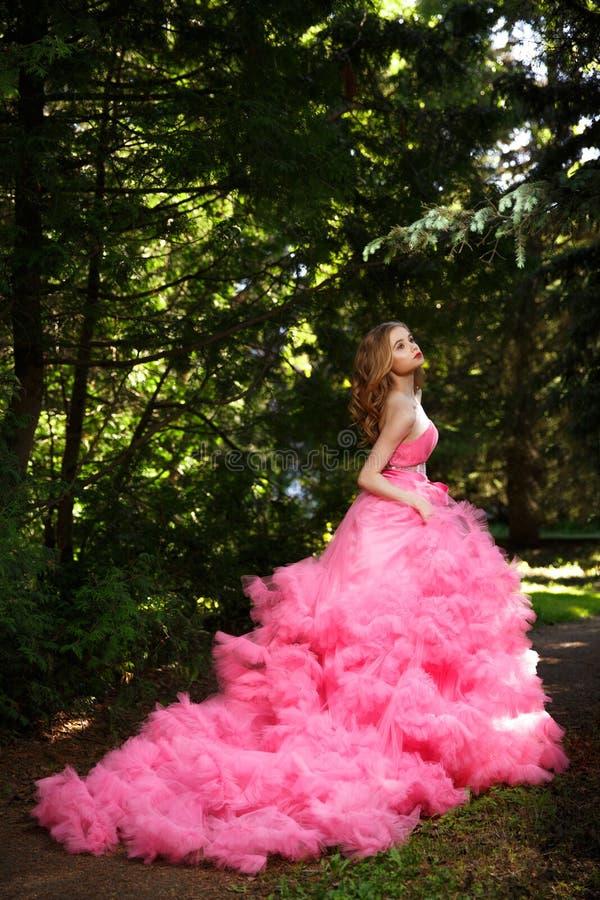 Het mooie meisje in roze avondjurk met pluizige rok stelt in botanische die tuin op het gras door het hout wordt omringd royalty-vrije stock fotografie