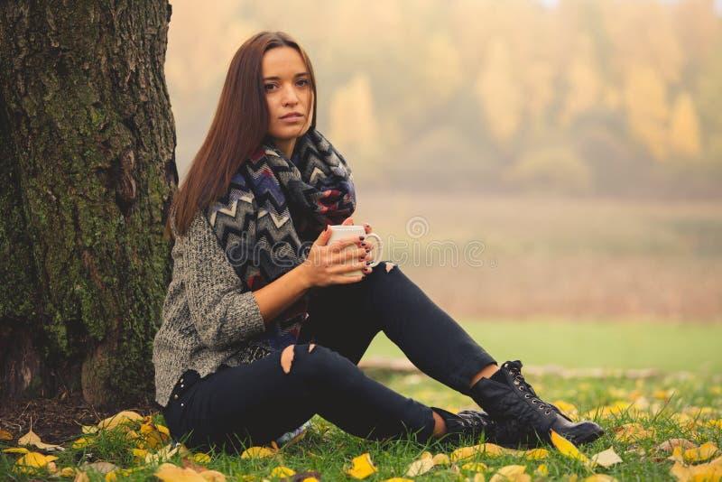 Het mooie meisje rusten en het drinken koffiezitting in de herfsttuin stock afbeeldingen