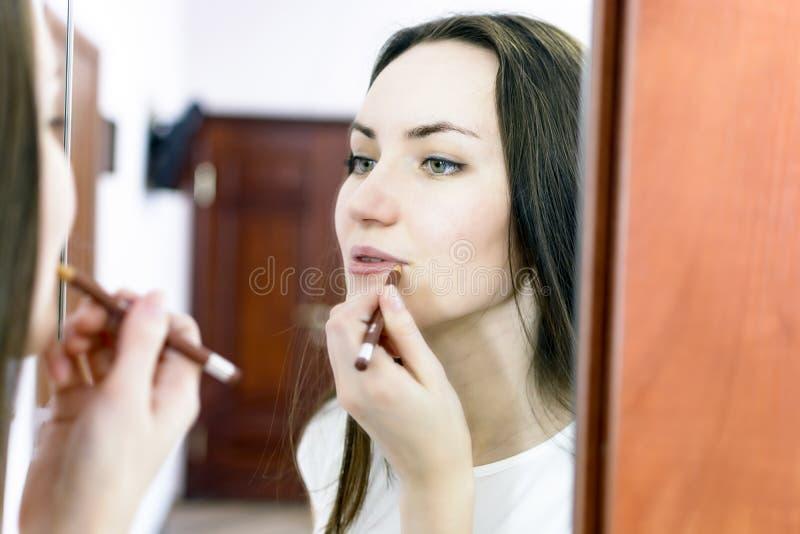 Het mooie meisje schildert lippen in het bureau royalty-vrije stock fotografie