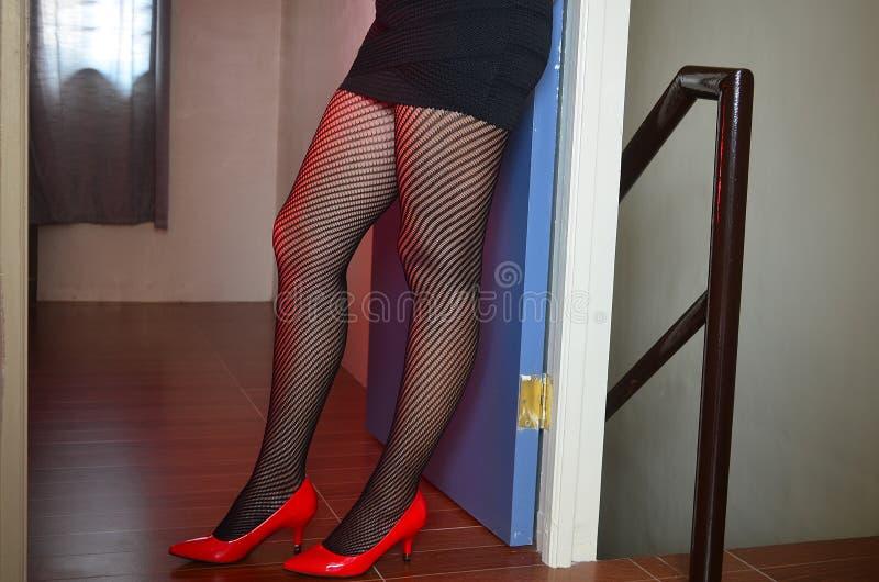 Het mooie meisje in sexy uitrusting stelt in een rood licht stock afbeelding
