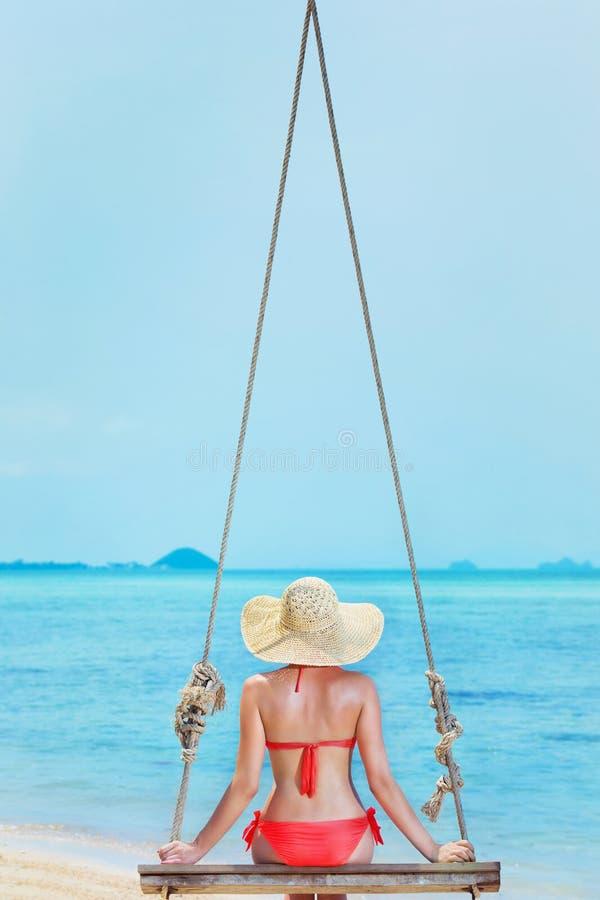 Het mooie meisje slingert bij de overzeese achtergrond op een vakantie royalty-vrije stock foto