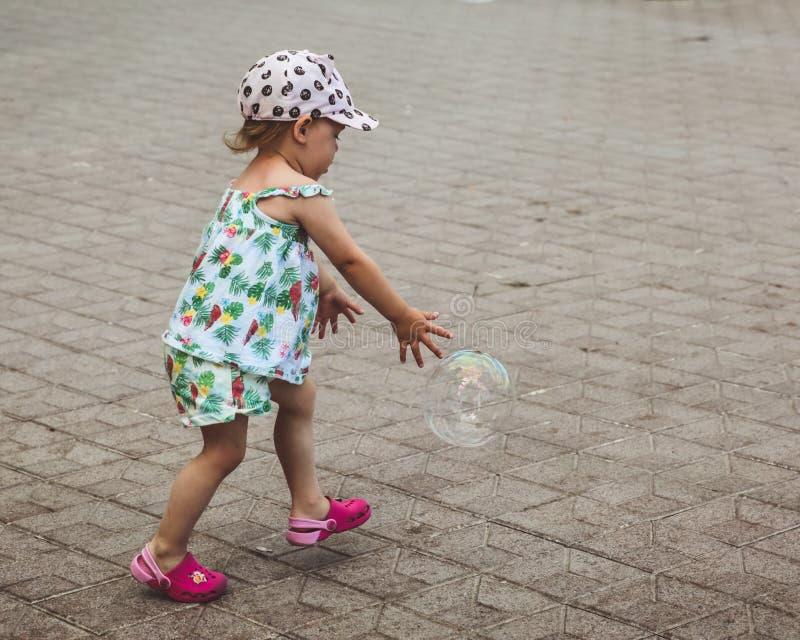 Het mooie meisje speelt met grote bellen in straat in de zomerdag royalty-vrije stock afbeeldingen
