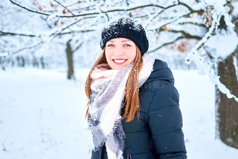 Het mooie meisje spelen met sneeuw in park stock foto