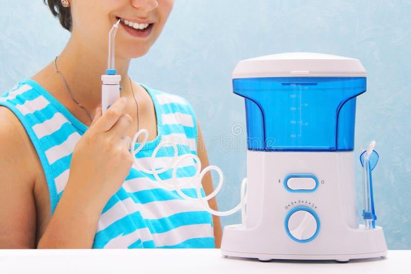 Het mooie meisje spoelt haar tanden met een mondelinge irrigator de vrouw glimlacht en houdt het irrigatorhandvat het schoonmaken stock foto's
