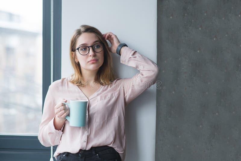 Het mooie meisje stellen dichtbij de muur in het bureau met een kop van koffie in zijn handen Koffiepauze in het bureau stock afbeeldingen