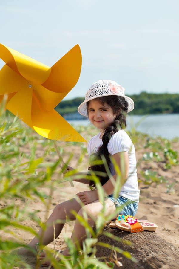 Het mooie meisje stellen met windmolen in park royalty-vrije stock afbeeldingen