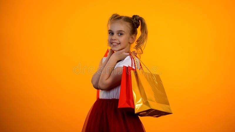Het mooie meisje stellen met het winkelen zakken aan nok, verkoop en kortingen, malplaatje stock foto's