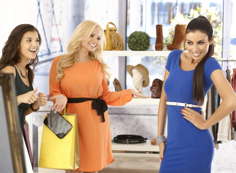 Het mooie meisje stellen in nieuwe kleding bij klerenopslag stock foto
