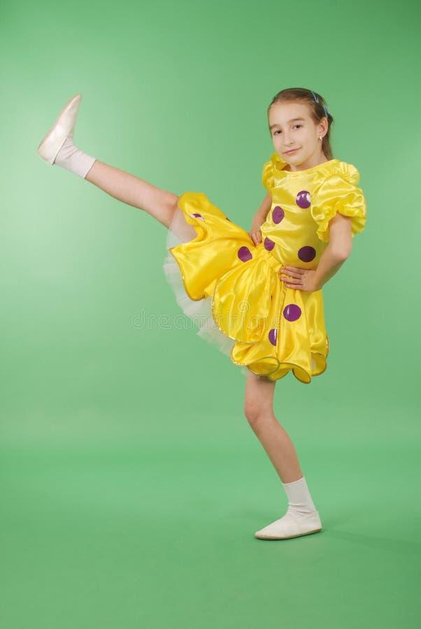 Het mooie meisje stellen voor de camera, in een gele korte kleding royalty-vrije stock fotografie