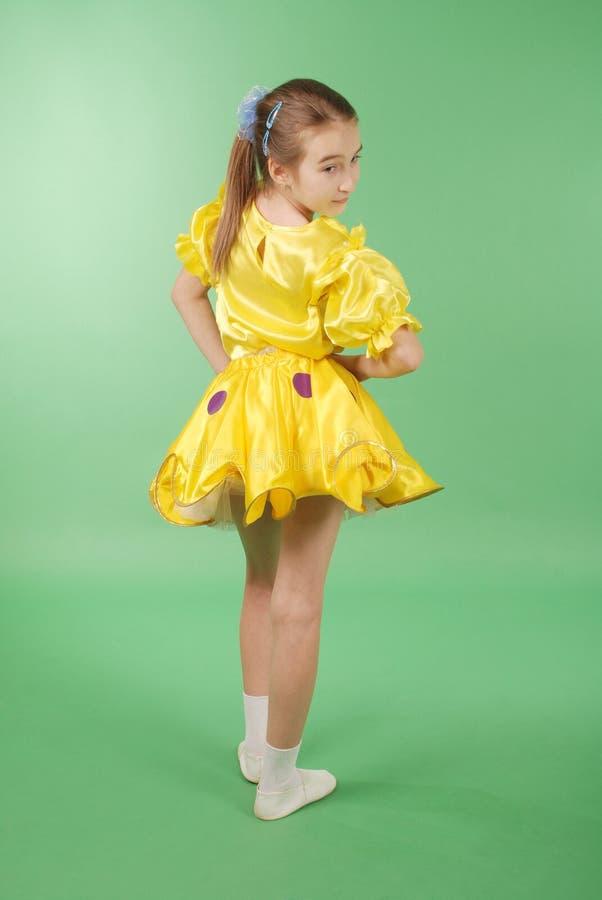 Het mooie meisje stellen voor de camera, in een gele korte kleding stock foto