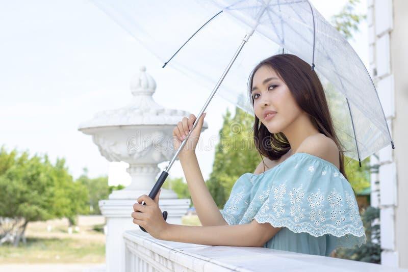Het mooie meisje van Aziatische verschijning bevindt zich met transparante paraplu Portret van een meisje stock afbeelding