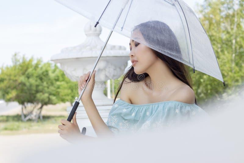 Het mooie meisje van Aziatische verschijning bevindt zich met transparante paraplu Portret van een meisje royalty-vrije stock foto