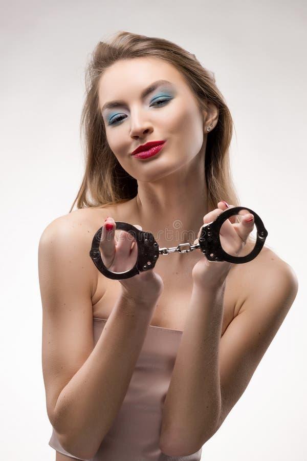 Het mooie meisje van blonde rode lippen glimlacht en houdt handcuffs royalty-vrije stock afbeelding