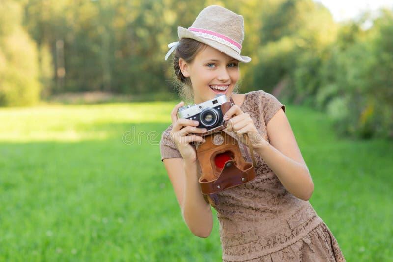 Het mooie meisje van de tienerleeftijd met retro camera stock afbeeldingen