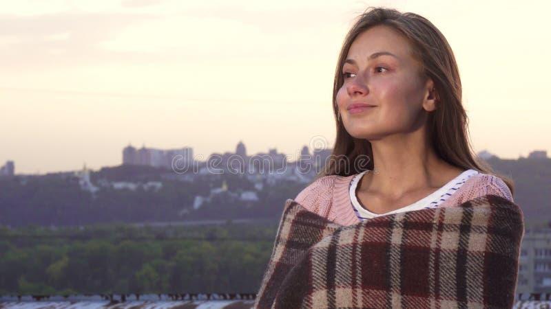 Het mooie meisje verbergen achter een deken en het genieten van de van mening van het dak stock fotografie