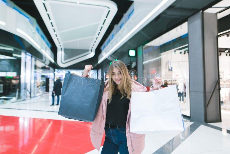 Het mooie meisje verheugt zich in het winkelen Portret van een meisje met het winkelen zakken op de achtergrond van winkelcomplex stock foto's