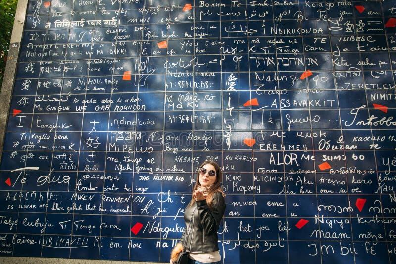 Het mooie meisje is walkin in Parijs dichtbij de basiliek de muur van de liefde stock afbeelding