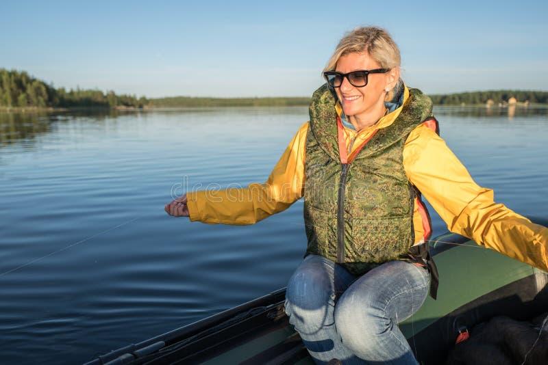 Het mooie meisje zet op de boot met vislijn in haar handen stock afbeeldingen