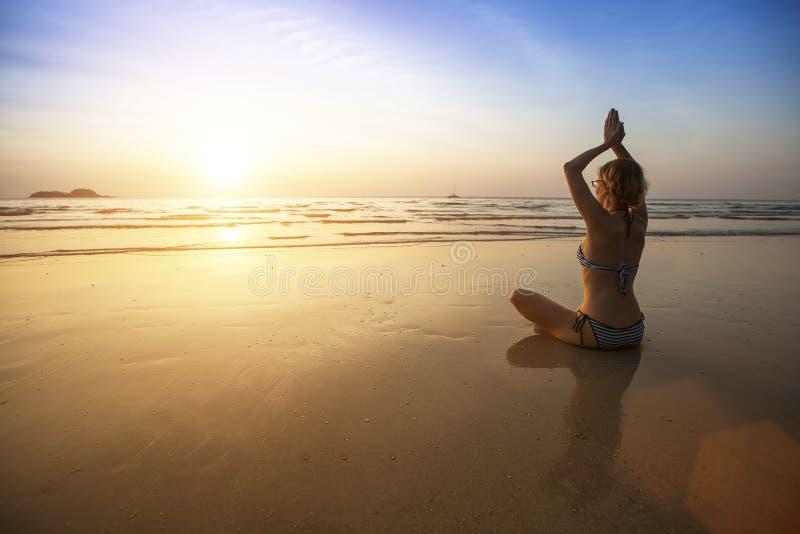 Het mooie meisje zit bij de kust en mediterend in yoga stel royalty-vrije stock afbeeldingen