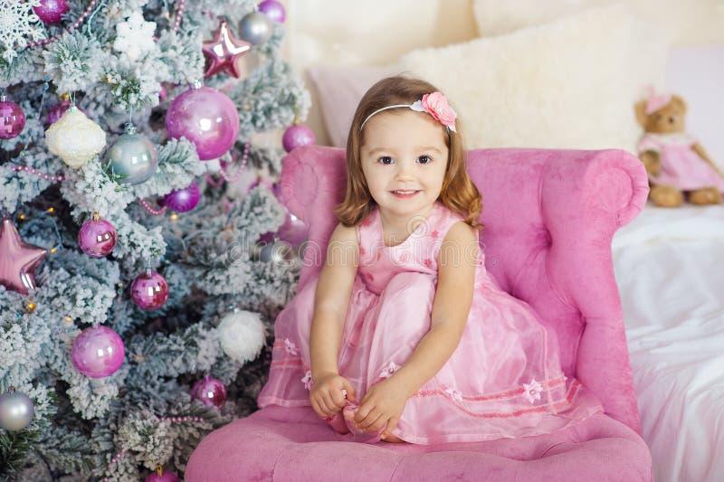 Het mooie meisje zit en stelt op een stoel achtergrond feestelijke sparrenreeks heldere branden Zacht glimlachen stock afbeeldingen