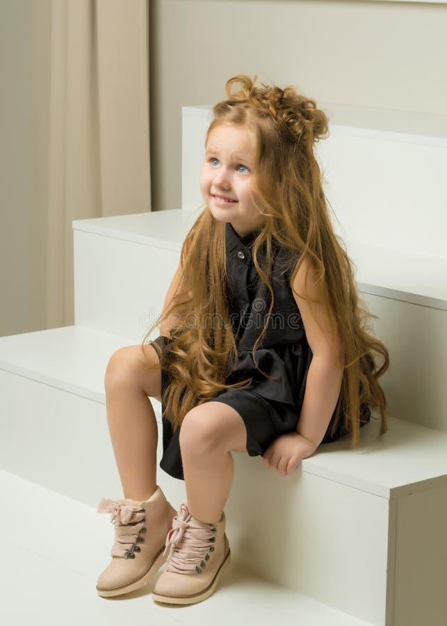 Het mooie meisje zit op de witte trap royalty-vrije stock afbeelding