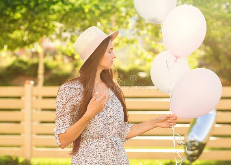 Het mooie meisje zit op het gras in een hoed en een mooie kleding stock foto's