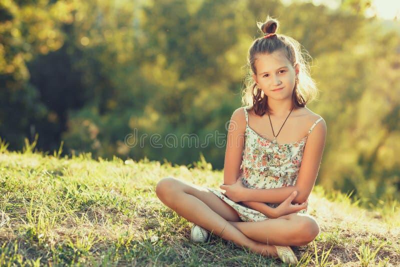 Het mooie meisje zit op het gras en bekijkt de camera Gekleed in sarafan royalty-vrije stock afbeeldingen