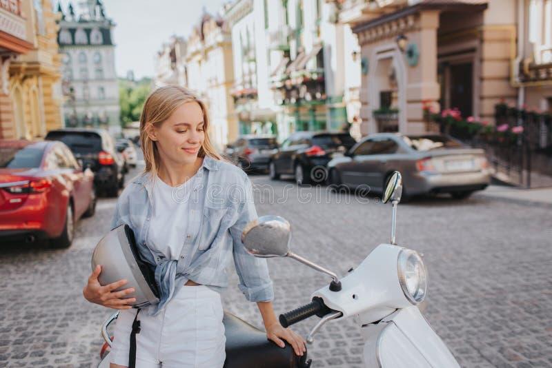 Het mooie meisje zit op motorfiets en bekijkt het Zij houdt helm in hand en glimlacht Het meisje is gelukkig royalty-vrije stock foto's