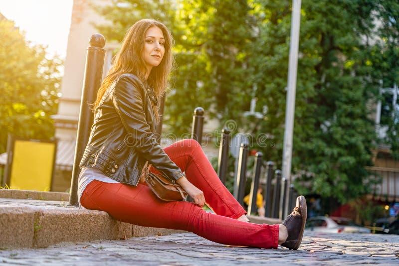 Het mooie meisje zit in openlucht op de bestrating De fotografie van de straatmanier met vrouwelijk model met backlightzon stock foto's