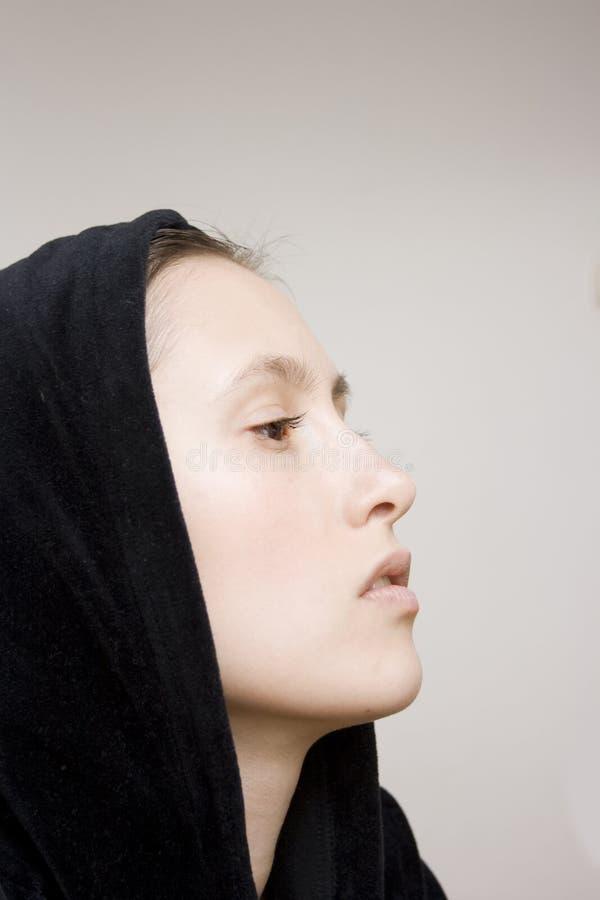 Het mooie meisje in zwarte kap, sluit omhoog royalty-vrije stock afbeeldingen