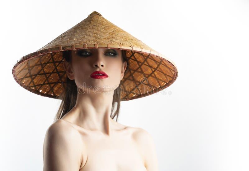 Het mooie meisjesmodel met rode lippen maakt en naakte schouders die Aziatische Vietnamese die kegelhoed dragen van riet wordt ge royalty-vrije stock foto