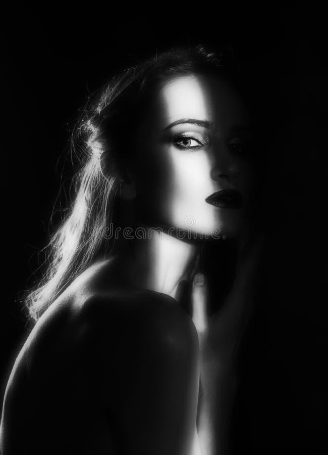 Het mooie meisjesmodel met rode lippen maakt omhooggaande en naakte schouders in de schaduw, met een aangestoken silhouet en een  royalty-vrije stock foto's