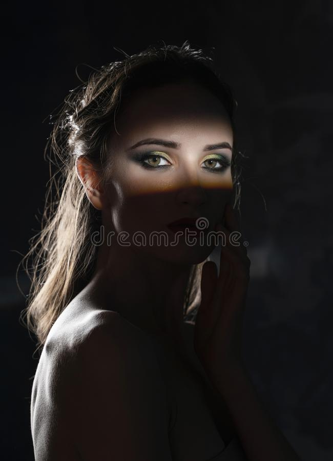 Het mooie meisjesmodel met rode lippen maakt omhooggaande en naakte schouders in de schaduw, met een aangestoken silhouet en een  stock fotografie