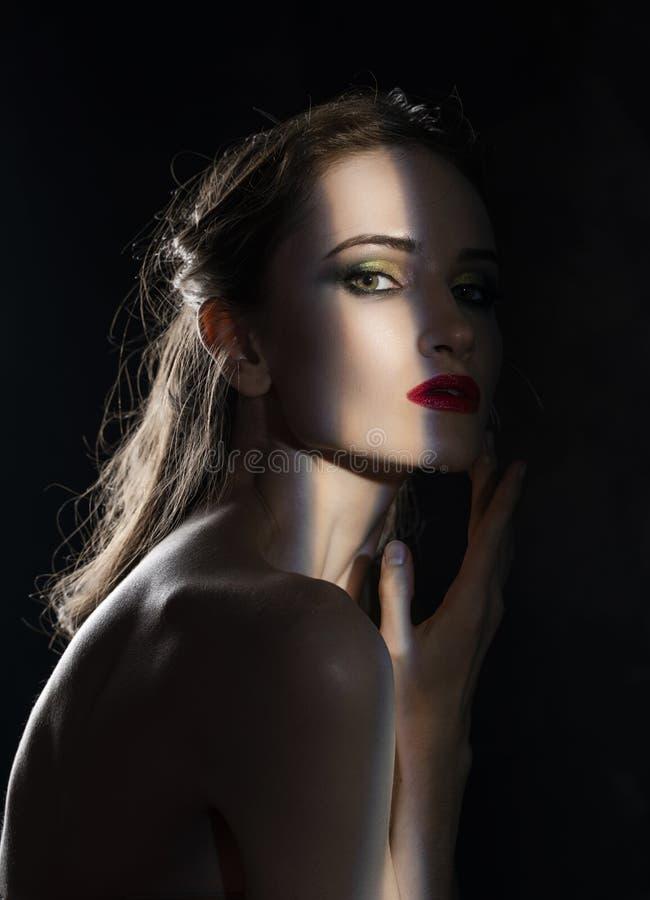 Het mooie meisjesmodel met rode lippen maakt omhooggaande en naakte schouders in de schaduw, met een aangestoken silhouet en een  royalty-vrije stock fotografie
