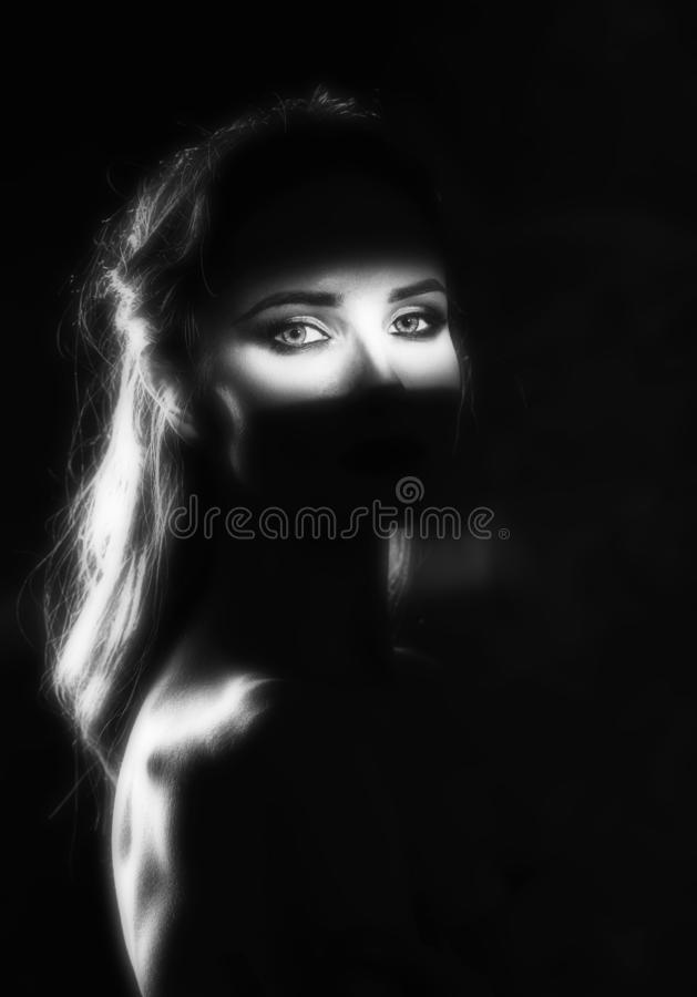 Het mooie meisjesmodel met rode lippen maakt omhooggaande en naakte schouders in de schaduw, met een aangestoken silhouet en een  royalty-vrije stock afbeelding