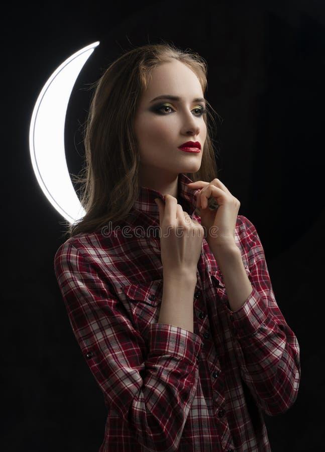 Het mooie meisjesmodel met rode lippen maakt op, dragend toevallig plaidoverhemd dichtbij een rond licht op een zwarte achtergron royalty-vrije stock foto