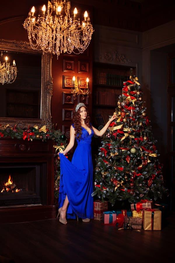Het mooie meisjesmodel viert Kerstmis of Nieuwjaar in een klassiek binnenland, dichtbij een Nieuwjaarboom, sparren Vakantievrouw  royalty-vrije stock fotografie