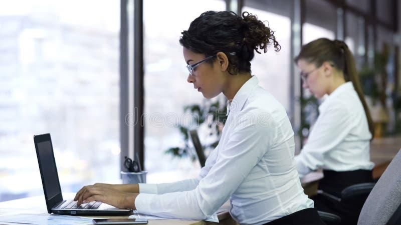 Het mooie mengen-rasdame typen op laptop, die voor het centrum van de bedrijfsteun werken royalty-vrije stock foto's