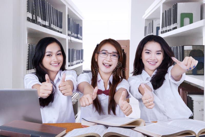 Het mooie middelbare schoolstudenten geven beduimelt omhoog stock afbeelding