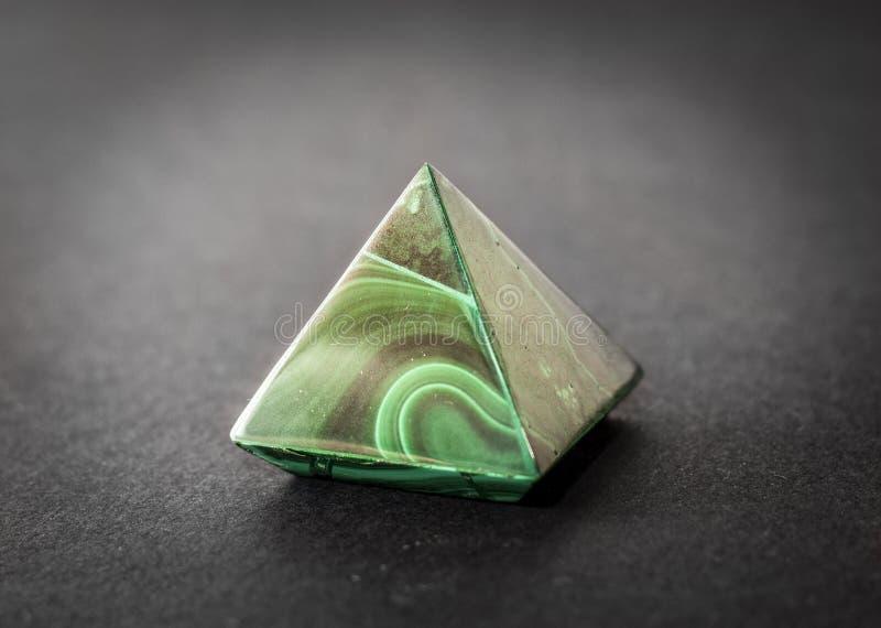 Het mooie mineraal van de malachietpiramide op donkere achtergrond royalty-vrije stock afbeeldingen