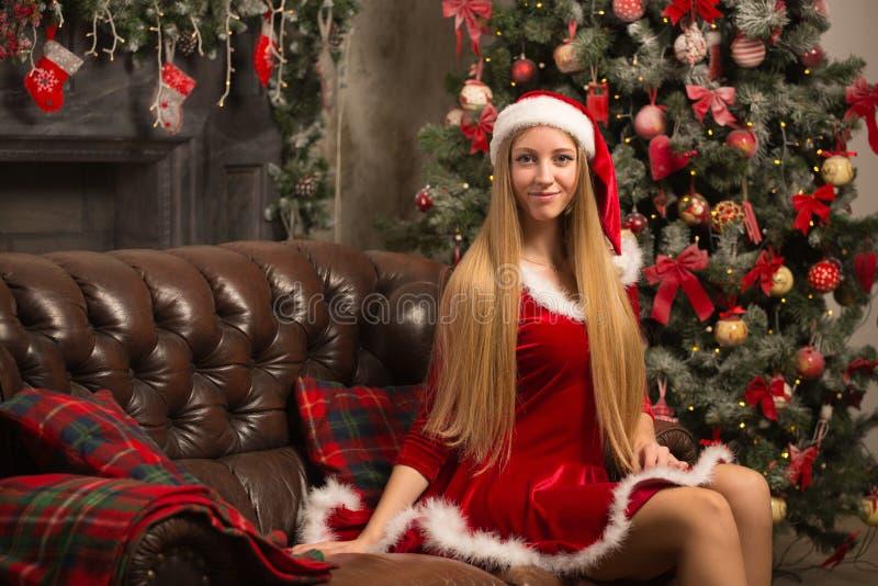 Het mooie model kleedde zich als Kerstman met dichtbij een Kerstboom royalty-vrije stock foto