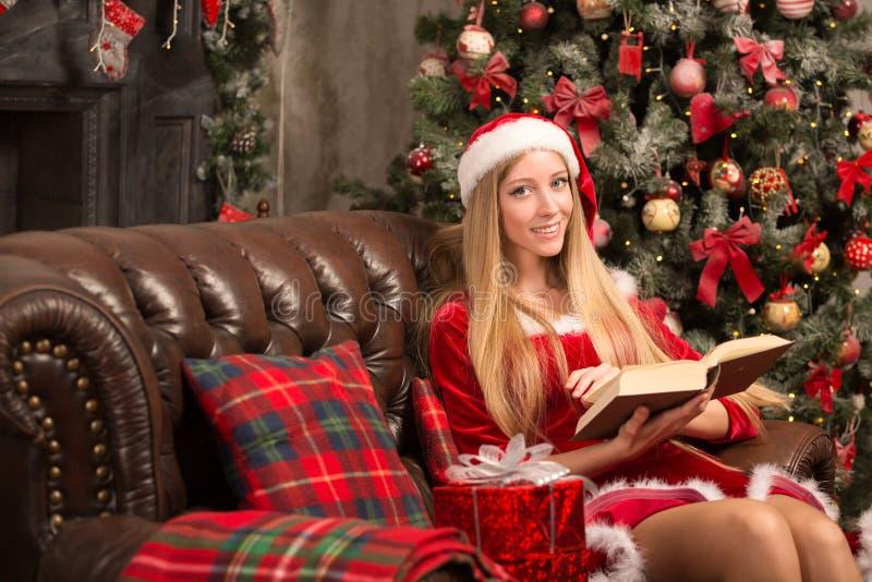 Het mooie model kleedde zich als Kerstman met dichtbij een Kerstboom royalty-vrije stock foto's