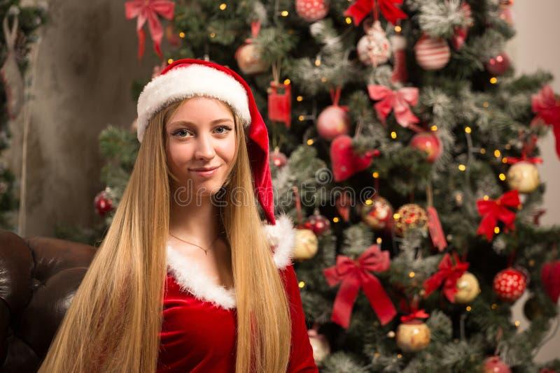 Het mooie model kleedde zich als Kerstman met dichtbij een Kerstboom stock afbeeldingen